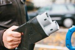Le conducteur prend un câble pour charger le véhicule électrique Un mode de transport moderne et qui respecte l'environnement qui Images stock