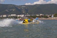 Le conducteur une moto de l'eau étend le tour raide et arrose l'eau de la banane gonflable de passagers Gelendzhik Photographie stock libre de droits