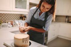 Le confiseur décore un gâteau photos stock