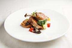 le confit Bien-bruni et croquant de canard avec le fenouil de rôti, les agrumes et le pruneau sauce Patte rôtie de canard Plat bl Photos libres de droits