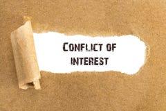 Le conflit d'intérêt des textes apparaissant derrière le papier brun déchiré photo stock