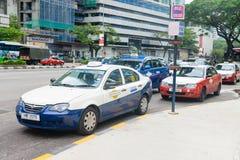 Le confort bleu et l'econom rouge Kuala Lumpur roulent au sol des voitures Images libres de droits