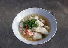 Le congee de riz s'est mélangé à la crevette, poisson, calmar et le porc, garnissent avec la coriandre Image libre de droits