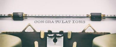Le congratulazioni esprimono sopra su Libro Bianco in macchina da scrivere Fotografie Stock