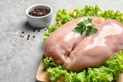Le conseil en bois avec des blancs de poulet crus et la laitue près des poivrons se mélangent dans la cuvette image libre de droits