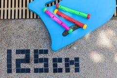 Le conseil et le jouet de natation s'étendent sur le plancher de piscine Images stock