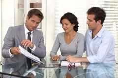 Le conseiller financier présente des investissements de banque à un jeune couple Photos stock