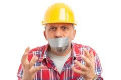 Le constructeur avec la bouche a fermé faire le geste désespéré photo stock