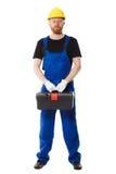 Le constructeur d'homme dans l'uniforme tient une boîte à outils Photographie stock