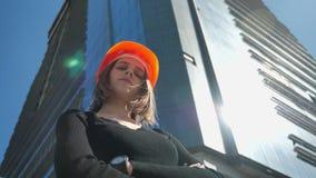 Le constructeur de jeune fille avec le casque se tient avec des bras croisés pendant la journée en été, concept de construction,  banque de vidéos