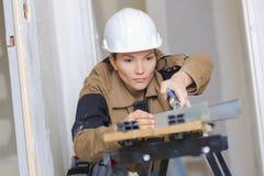 Le constructeur féminin utilisant la table électronique de machine a vu la coupe Image libre de droits