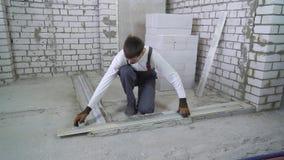 Le constructeur fait des mesures sur le radier de b?ton avec des r?gles de coin et de construction banque de vidéos