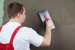 Le constructeur fonctionnant applique la colle sur un mur pour un carreau de céramique f Photo libre de droits
