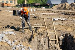 Le constructeur grésille le sable avec une pelle dans le puits photographie stock libre de droits
