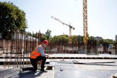 Le constructeur habillé dans le gilet et le casque oranges de travail emploie un ruban métrique sur le chantier images stock