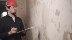 Le constructeur principal vérifie la qualité des revêtements muraux pendant les travaux de réparation clips vidéos