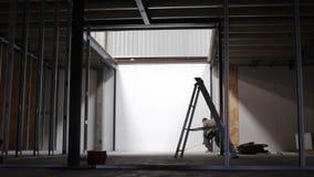 Le constructeur prolonge le ruban métrique sur le chantier de construction clips vidéos
