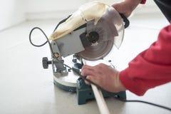 Le constructeur utilisant une petite circulaire électrique a vu pour couper une longueur de p Photographie stock libre de droits