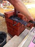 Le constructeur utilise une truelle pour des briques de maçonnerie image libre de droits