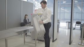 Le contrôle d'homme d'affaires un bagage sur la machine de rayon X et passent par le point de contrôle de rayon X clips vidéos