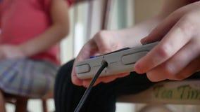 Le contrôleur de jeux vidéo de jeu d'enfants d'enfants à l'intérieur consolent le garçon et la fille jouent le gamepad en ligne l banque de vidéos