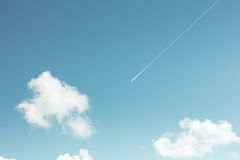 Le contrail d'une avion de ligne de message publicitaire strie à travers un bleu de sarcelle d'hiver photos stock