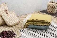 Le coperte ed il rattan insacca sulla tavola con le ciliege sul terrazzo della casa Foto reale fotografia stock