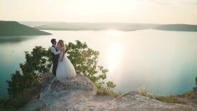 Le coppie abbracciano delicatamente stare sull'orlo della scogliera e considerare il lago video d archivio
