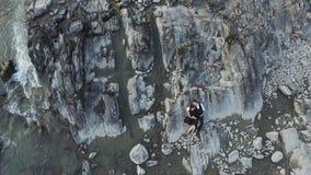 Le coppie abbracciano insieme la bugia sulla costa selvaggia della scogliera archivi video