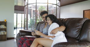 Le coppie abbracciano la seduta sulla vettura Using Tablet Computer che parla nel salone, nel giovane e nella donna passanti in r archivi video