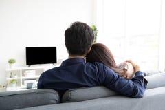 Le coppie adolescenti asiatiche stabiliscono il contatto oculare che si rilassa sul sofà dal fotografia stock libera da diritti