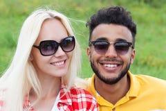 Le coppie affrontano vicino su erba verde, sull'uomo della corsa della miscela e sugli occhiali da sole all'aperto della donna Fotografia Stock