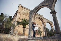 Le coppie alla moda di nozze si avvicinano alla chiesa cattolica Sposa e sposo Ritratto esterno immagini stock
