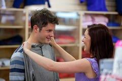 Le coppie allegre che scelgono i vestiti in vestiti acquistano Immagini Stock