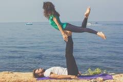 Le coppie allegre stanno praticando l'yoga sulla spiaggia Immagini Stock Libere da Diritti