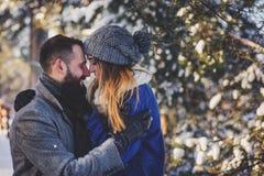 Le coppie amorose felici che camminano nella foresta nevosa dell'inverno, spendente il natale vacation insieme Fotografie Stock