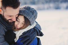 Le coppie amorose felici che camminano nella foresta nevosa dell'inverno, spendente il natale vacation insieme Attività stagional Immagine Stock