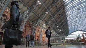 Le coppie anziane camminano dopo la statua nella stazione ferroviaria di re Cross St Pancras stock footage