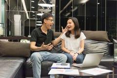 Le coppie asiatiche felici stanno lavorando insieme e stanno parlando alla notte fotografia stock