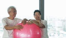 Le coppie asiatiche senior felici si divertono con la classe della palla di yoga della palestra Immagini Stock Libere da Diritti