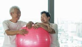Le coppie asiatiche senior felici si divertono con la classe della palla di yoga della palestra Fotografie Stock Libere da Diritti