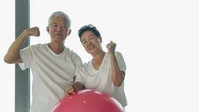 Le coppie asiatiche senior felici si divertono con la classe della palla di yoga della palestra Fotografia Stock