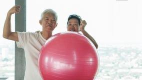 Le coppie asiatiche senior felici si divertono con la classe della palla di yoga della palestra Immagini Stock