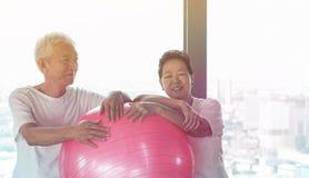 Le coppie asiatiche senior felici si divertono con la classe della palla di yoga della palestra Immagine Stock