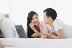 Le coppie asiatiche si trovano incline sul letto in camera da letto immagini stock