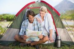 Le coppie attraenti che si siedono dalla loro lettura della tenda tracciano Fotografia Stock