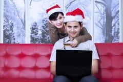 Le coppie attraenti pagano online nel giorno di natale Fotografia Stock