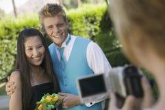 Le coppie ben vestito dell'adolescente che posano per la videocamera fuori della scuola ballano immagine stock