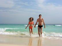 Le coppie camminano dall'oceano Fotografia Stock