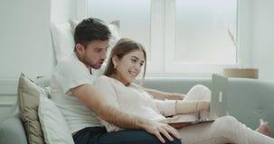Le coppie carismatiche stesse che sorridono e felici fanno un ordine dal taccuino di mattina sul sofà sia in pigiami video d archivio